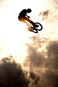 Young man jumps with BMX bike over ramp, Munich, Bavaria, Germany