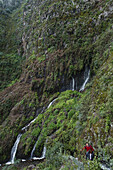 Couple hiking near the waterfall, Galeria de agua, Fuente Marcos, Fuentes Marcos y Cordero, natural preserve, Parque Natural de las Nieves, east side of extinct volcanic crater, Caldera de Taburiente, above San Andres, UNESCO Biosphere Reserve, La Palma,