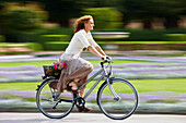Mature woman riding bicyle, Munich, Bavaria, Germany