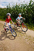Two children (6-7 years) riding bicycles, Bavaria, Germany