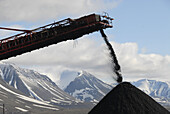 Mountain of coal pours out of mountain on a conveyor belt to be trucked to the port,  Svea coal mine,  Svalbard,  Norway