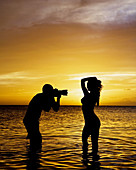 man shooting nude model in sunset.