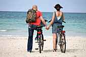 Adult, Adults, back view, Backpack, Backpacks, beach, beaches, bicycle, bicycles, bike, bikes, biking, Calm, Calmness, Color, Colour, Contemporary, couple, couples, cycle, cycles, Daytime, exterior, female, Full body, Full length, Full-body, Full-length,