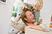 Action, Activity, Adult, Adults, Amusement, At home, Blond, Blonds, boy, boys, Caucasian, Caucasians, child, children, Choke, Choking, Color, Colour, Contemporary, dad, Daytime, Expressive, Expressiveness, Fair-haired, families, family, father, fathers, F