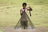 Cambodian fisherman with fishing net in a river, Angkor, Siem Reap Province, Cambodia, Asia