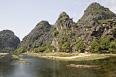 Karst mountains at a river in the sunlight, Ninh Binh Province, Vietnam, Asia