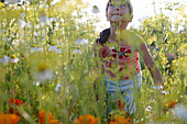 Girl (6-7 years) smelling flowers, Lower Saxony, Germany