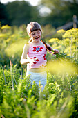 Girl (6-7 years) holding carrot, Lower Saxony, Germany