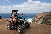 Couple on a quad all-terrain vehicle near Ponta da Canaveira, Porto Santo, near Madeira, Portugal