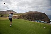 Golfer tees off at hole 14 at Porto Santo Golfe Golf Course, Porto Santo, near Madeira, Portugal