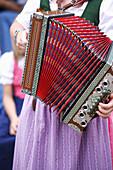 Woman playing harmonica, Styria, Austria
