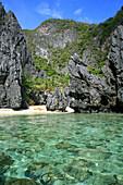 Palm-lined sandy beach on an uninhabited limestone island in the sunlight, Bacuit Archipelago, El Nido, Palawan, Philippines