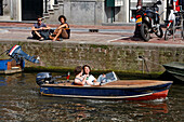 A Pleasure Boat With Two Young People Drinking A Beer On A Canal, Amsterdam, Netherlands, Holland
