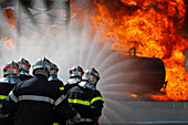 A Team With 2 Hoses Approaching A Fire On A Tanker At A Loading Station. Training Of The Firefighters Of The Sdis38 In Hydrocarbon Fires, Gesip (Study Group Of Safety In The Petrol And Chemical Industries) Of Roussillon, Isere (38), France