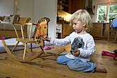 Mädchen (2 Jahre) spielt mit einem Schaukelpferd, Berg, Bayern, Deutschland