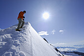 Mountaineer ascending on snow covered ridge towards Hochfeiler, Zillertal Alps, South Tyrol, Italy