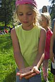 Girls holding a spider in hand, Bavarian Alps, Upper Bavaria, Bavaria, Germany