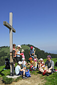 Group of hikers with children resting beside summit cross, Bavarian Alps, Upper Bavaria, Bavaria, Germany