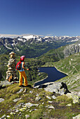 Woman looking over reservoir Lago della Sella  to Ticino Alps, Gotthard range, Canton of Ticino, Switzerland