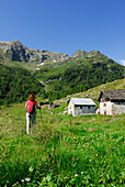 Woman hiking over mountain pasture with alpine huts, Valle Santa Maria, Ticino Alps, Canton of Ticino, Switzerland