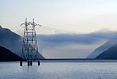 Electricity pylon in reservoir Lai da Sontga Maria, Lukmanier Pass, Adula Alps, Grisons, Switzerland