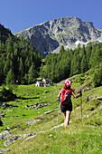 Woman walking near alpine hut, Alpe di Sfii, Pizzo dell'Alpe Gelato, Val di Campo, Ticino Alps, Ticino, Switzerland