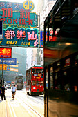 Double decker tram and neon signs in a street, Hong Kong, China