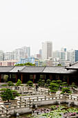 Yard of the Chi Lin nunnery with skyscrapers in the background, Kowloon, Hong Kong, China