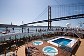 Pool deck of cruiseship MS Delphin Voyager as vessel approaches Ponte 25 de Abril Bridge on Tagus River, Lisbon, Lisboa, Portugal