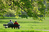 couple sitting on a bench in Georgengarten, Herrenhausen, Hannover, Germany