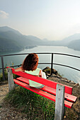 Woman sitting on a bench while enjoying view over Lake Lugano, Morcote, Ticino, Switzerland