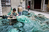 Female tailor working on fishing nets on the street, Jinfeng, Changle, Fujian province, China, Asia