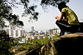 Young woman on a rock with view over the city, district Siming, Xiamen, Fujian province, China, Asia