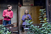 Old chinese woman and german tourist at the courtyard of a roundhouse of the Hakka, Hongkeng, Longyan, Fujian, China, Asia