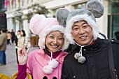 Portrait of a Chinese couple with funny winter hats in the shopping street Nanjing Lu, Shanghai, China, Asia