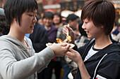 Two young women eating outside the Huxinting Teahouse, Yu Yuan Garden, Nanshi, Feng Shui, Shanghai, China, Asia