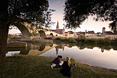 Two young girls sitting on the banks of the river, Stone bridge and Regensburg cathedral, cathedral of St. Peter, Unesco World Cultural Heritage, Donau, Regensburg, Upper Palatinate, Bavaria, Germany, Europe
