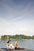 Junge Frau liegt auf einem Steg am Starnberger See, hört Musik, Bayern, Deutschland