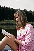 Young woman reading a book, lake Starnberg, Bavaria, Germany