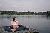 Young woman lying on a jetty while reading a book, lake Starnberg, Bavaria, Germany