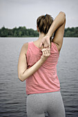 Junge Frau beim Stretching am Starnberger See, Bayern, Deutschland