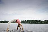 Junge Frau macht eine Brücke auf einem Steg am Starnberger See, Bayern, Deutschland