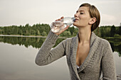 Young woman drinking a bottle of water, lake Starnberg, Bavaria, Germany