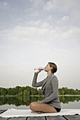 Young woman drinking a bottle of water while sitting on a jetty at lake Starnberg, Bavaria, Germany