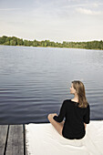 Young woman sitting on a yetty at lake Starnberg, Bavaria, Germany