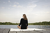 Young woman sitting on jetty at lake Starnberg, Bavaria, Germany