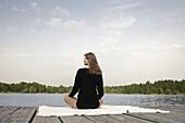 Junge Frau sitzt auf einem Steg am Starnberger See, Bayern, Deutschland