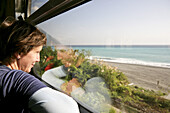 Young German women in the train looking out of the window, view at ocean and beach, Hualian, Republic of China, Taiwan, Asia