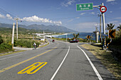 Cyclist on coast road in the sunlight, Highway No 11, Wushihbi, Republic of China, Taiwan, Asia