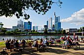 People sitting in the beer garden enjoying the Frankfurt skyline, Museum Embankment, Frankfurt am Main, Hesse, Germany